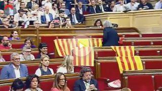 La diputada de Podemos Àngels Martínez Castells quita las banderas españolas de los escaños del PP en el Parlament.