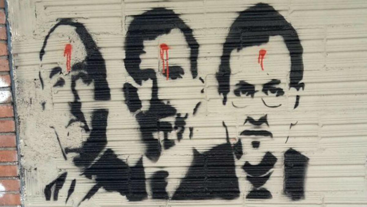 La pintura roja simula un tiro en la frente del Rey Felipe VI y el presidente Mariano Rajoy.