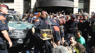 Varios miles de ciudadanos protestan por los registros de la Guardia Civil por el 1-O en la Rambla Catalunya, en Barcelona, donde se encuentra la consellería de Economía, mientras en Via Laietana, ante las sedes de Gobernación y Exteriores (en la imagen), centenares de personas realizan una sentada para impedir que los vehiculos policiales puedan moverse (Foto: Efe)