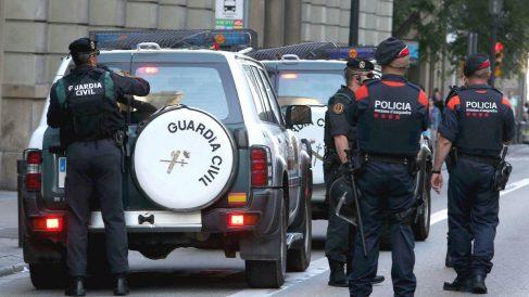 Un agente de la Guardia Civil junto a varios efectivos de los Mossos. (Foto: EFE)