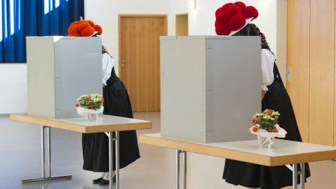 Dos mujeres alemanas votan con el tradicional bollenhut en un colegio de la Selva Negra. (AFP)