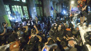 Agentes de los Mossos d'Esquadra custodian las puertas de la sede de la consellería de Economía de la Generalitat en cuyo interior se encontraba un grupo de agentes de la Guardia Civil que realizaban un registro con motivo del 1-O (Foto: Efe)