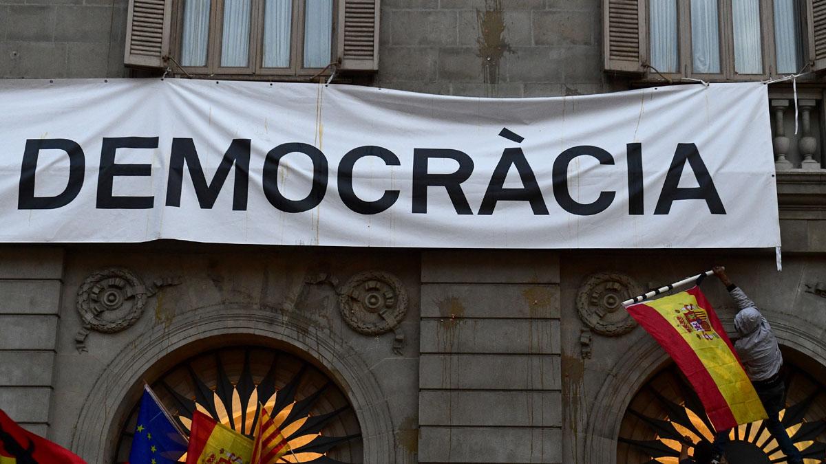 Manifestantes intentando descolgar la pancarta publicitaria del referéndum.