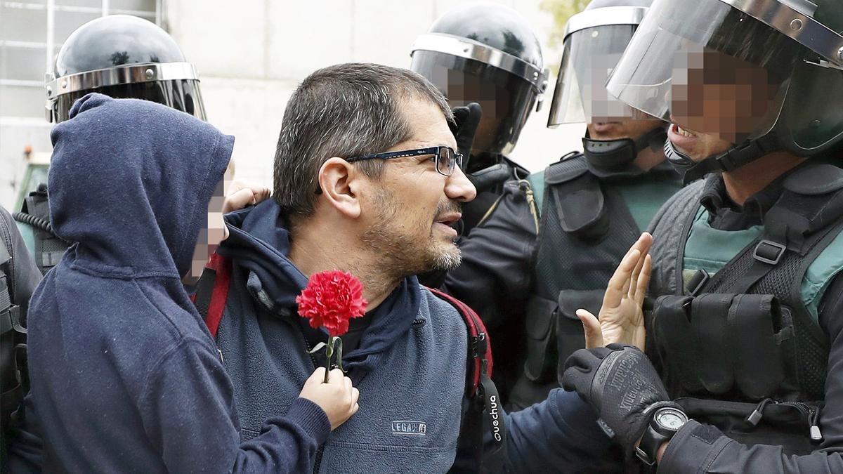 Un padre con su hijo mientras la Policía trata de desalojar un colegio en Gerona. (Foto: EFE)