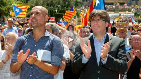 El ex jugador Josep Guardiola junto al presidente de la Generalitat, Carles Puigdemont. (Foto: EFE)