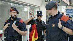 Un agente de la Policía Nacional saluda a dos mossos (Foto: EFE).