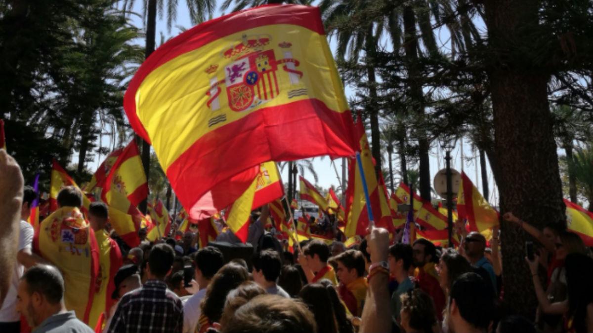 Manifestantes exhiben banderas españolas.