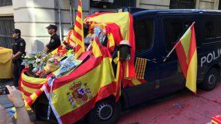 Así quedó el 8-O un furgón de la Policía Nacional, con flores y banderas depositadas por los manifestantes.