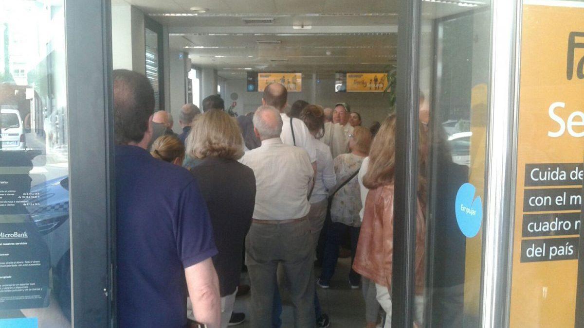 Filas de personas en La Caixa esperando su turno. FOTO: OKDIARIO