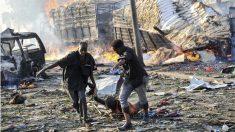 Dos hombres arrastran a una de las víctimas del atentado en Mogadiscio. (Foto: AFP)
