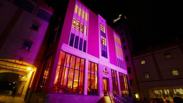 Una fábrica de Estrella Damm iluminada de color rosa por el Día Internacional del Cáncer de mama