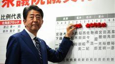 El primer ministro japonés, Shinzo Abe, marca con rosas los nombres de sus diputados electos en los comicios legislativos. (AFP)