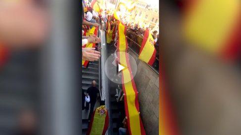 Un grupo de jóvenes llega a la manifestación de Barcelona portando una gran bandera de España.