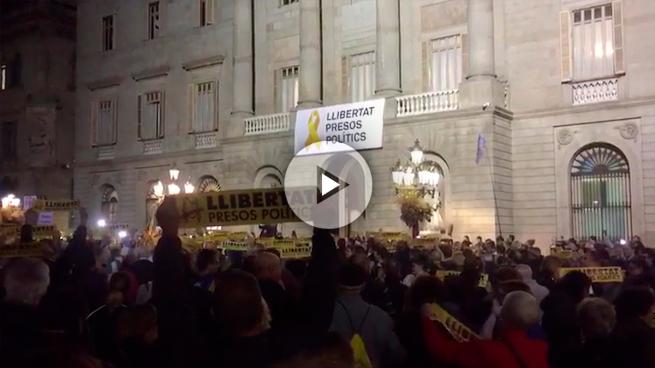 Independentistas protestan en Sant Jaume entre las dos banderas de España que presiden los edificios