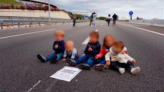 Cinco niños en mitad de una carretera con un cartel de los 'Jordis'