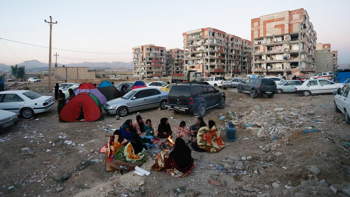 Un grupo de iraníes descansa a la intemperia tras la devastación de un terremoto el 12 de noviembre de 2017.(Foto: AFP)