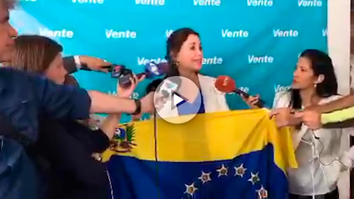 María Corina Machado se dirige a los medios, con la bandera venezolana entre las manos.