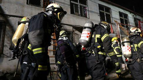 Bomberos ante la vivienda incendiada (Foto: AFP).