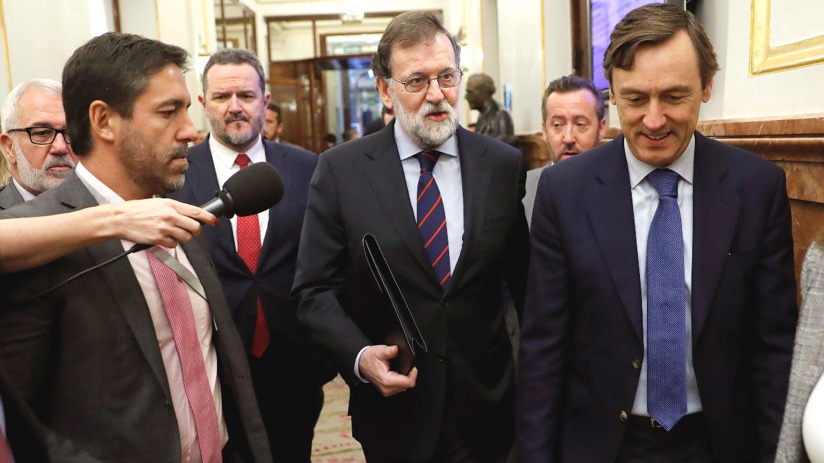 El presidente del Gobierno , Mariano Rajoy (c), junto al portavoz parlamentario del PP, Rafael Hernando (d), a la salida de la sesión de control al Ejecutivo celebrada hoy en el pleno del Congreso de los Diputados. (Foto: Efe)