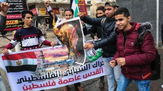 Jóvenes palestinos queman una fotografía de Donald Trump en Rafah. (Foto: AFP)