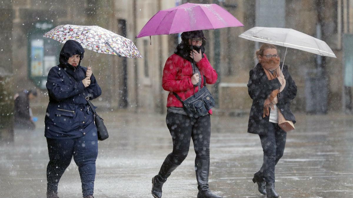 Varias personas en la calle con paraguas (Foto: EFE).