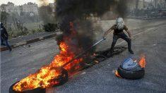 Un radical palestino mueve neumáticos ardiendo con una barra de hierro en el checkpoint de Qalandia, en las afueras de Ramala (Cisjordania). (AFP)
