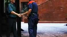 Un guardia civil y un agente de los Mossos d'Esquadra se saludan en la puerta de un edificio oficial (Foto: EFE).