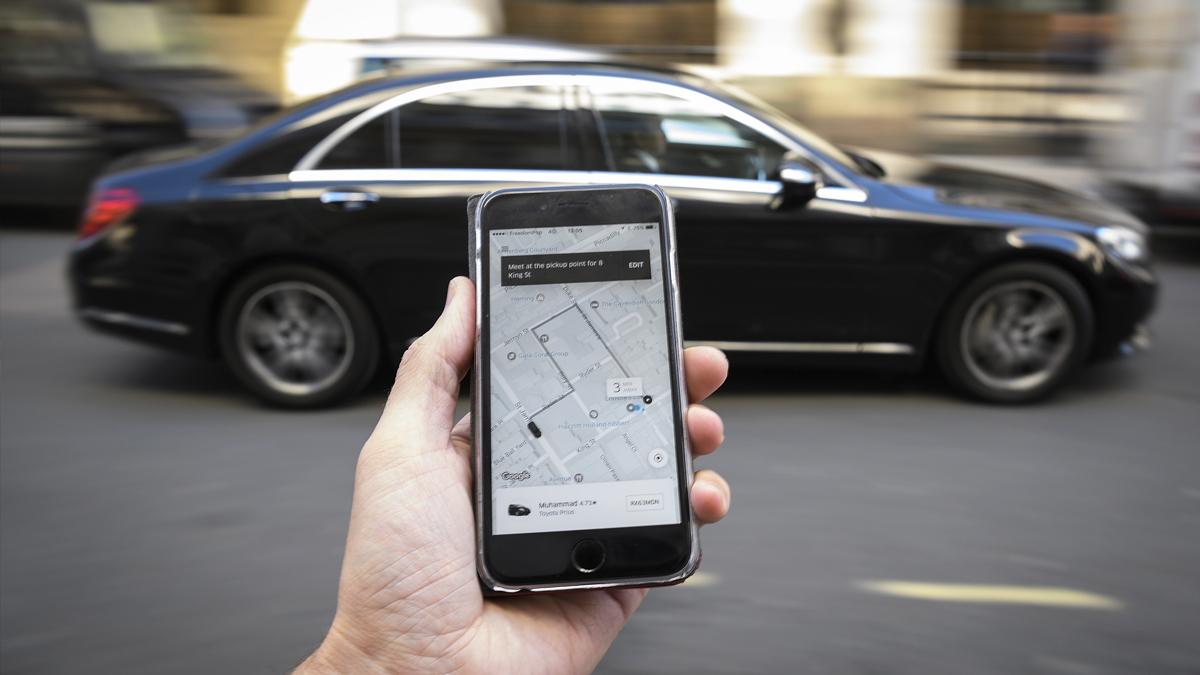 Aplicación de Uber con uno de los vehículos de la compañía de fondo. (Foto: Getty)