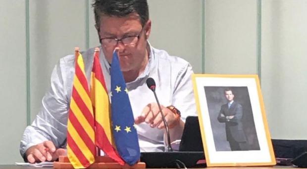El portavoz de C's en el Ayuntamiento de Calafell con las banderas europea, la catalana, la española y el retrato del Rey retirados de la sala de plenos.