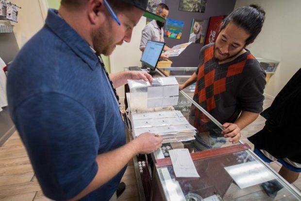 El encargado de un dispensario de marihuana en California le muestra a un cliente todas las variedades de 'wax', una resina extraída de la marihuana, disponibles. Foto: AFP