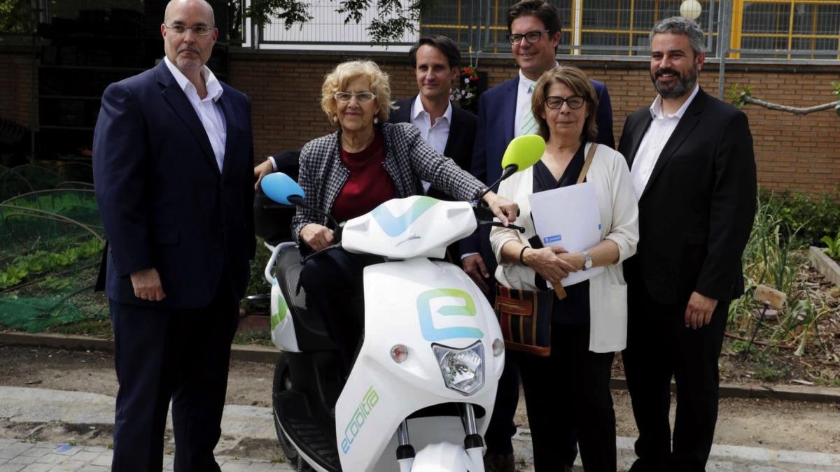 La alcaldesa en La alcaldesa Manuela Carmena presentando el servicio de alquiler de motos eléctricas junto a Marimón-Clos, primero por la derecha. (Foto: Madrid)mayo presentando el servicio de alquiler de motos eléctricas junto a Marimón-Clos, primero por la derecha. (Foto: Madrid)