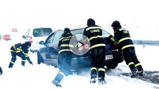 Efectivos de la UME empujan un coche atrapado por la nieve en la AP6 (Foto: Efe).