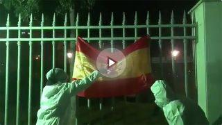 Dos cachorros de la CUP con la cara tapada quemando una bandera de España.