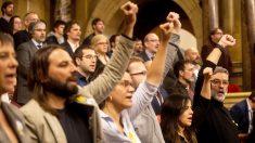 Diputados de la CUP, con Carles Riera al frente, entonan 'Els segadors' en el Parlament. (Foto: EFE)