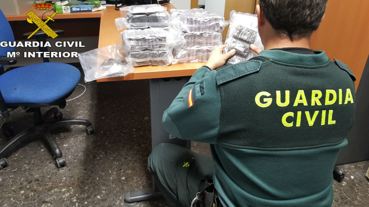 Un guardia civil manipula hachís intervenido. (Foto: Guardia Civil)