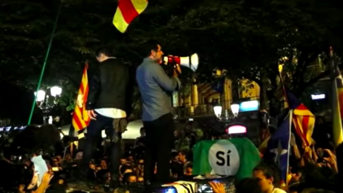 El presidente de Òmnium Cultural, Jordi Cuixart, y el de la ANC, Jordi Sánchez, encima de un coche de la Guardia Civil delante de la Consejería de Economía de la Generalitat.