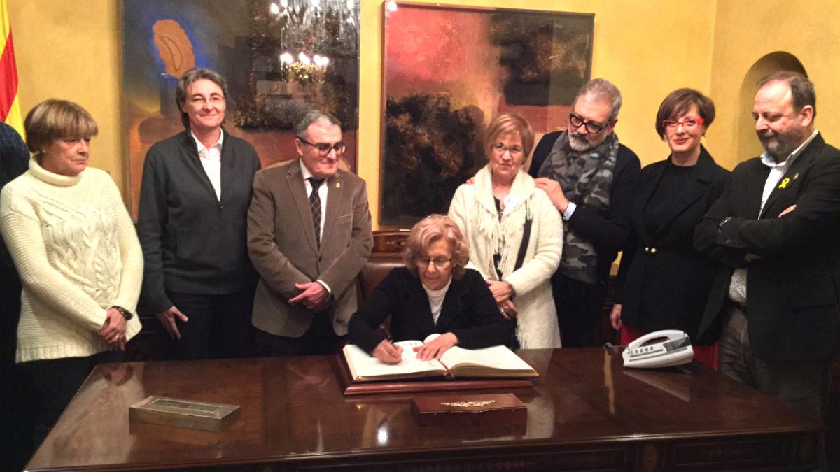 Carmena, firmando en el libro de honor del Ayuntamiento de Lérida.