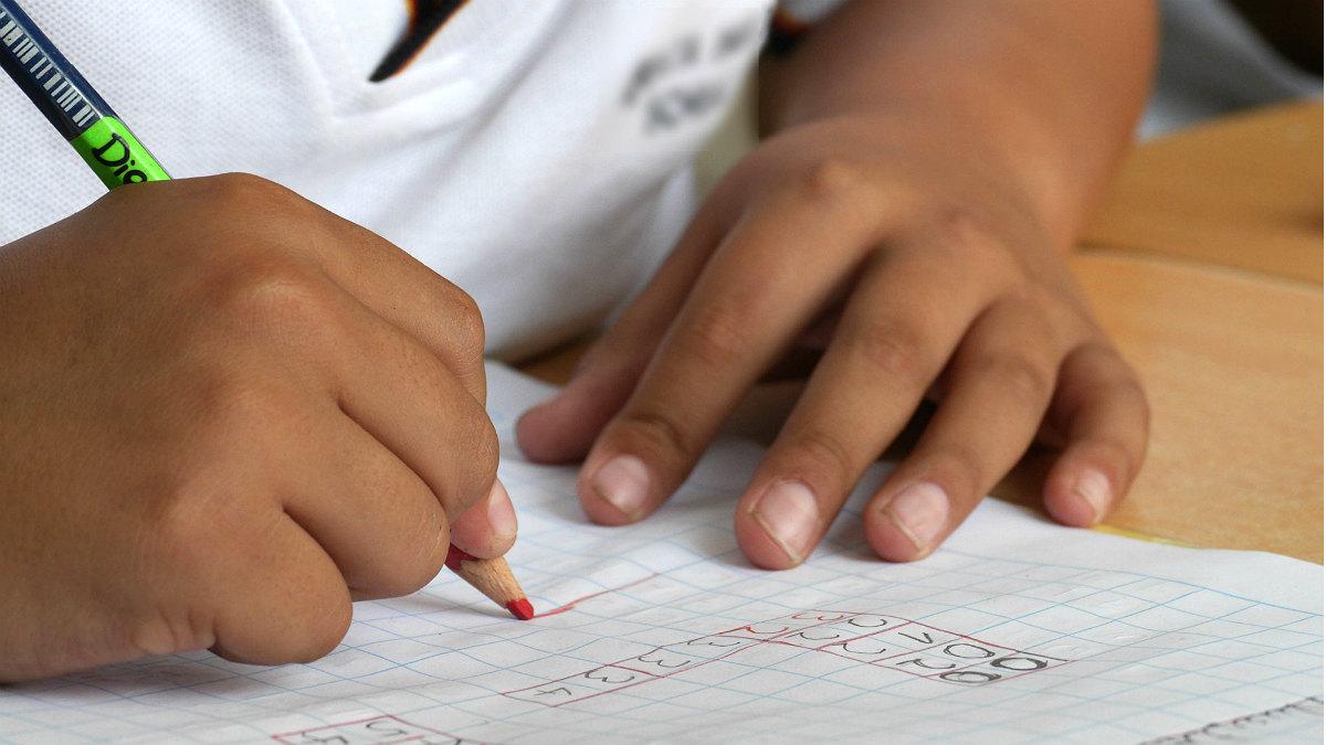 Un niño hace sus deberes en el colegio.