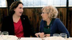 Las alcaldesas Ada Colau y Manuela Carmena se cogen de la mano en un restaurante del Puerto Olímpico de Barcelona. (EFE)
