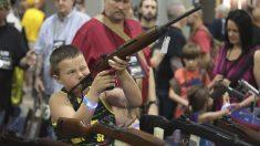 Un niño sostiene un arma en una feria de la Asociación Nacional del Rifle. (Foto: AFP)