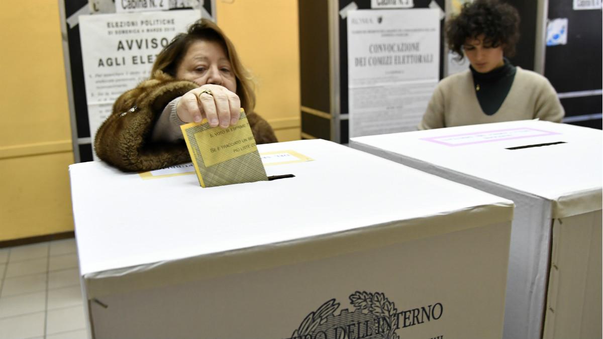 Una mujer introduce su papeleta en un colegio electoral de Roma, en las lecciones generales de Italia este 4-M. (AFP)