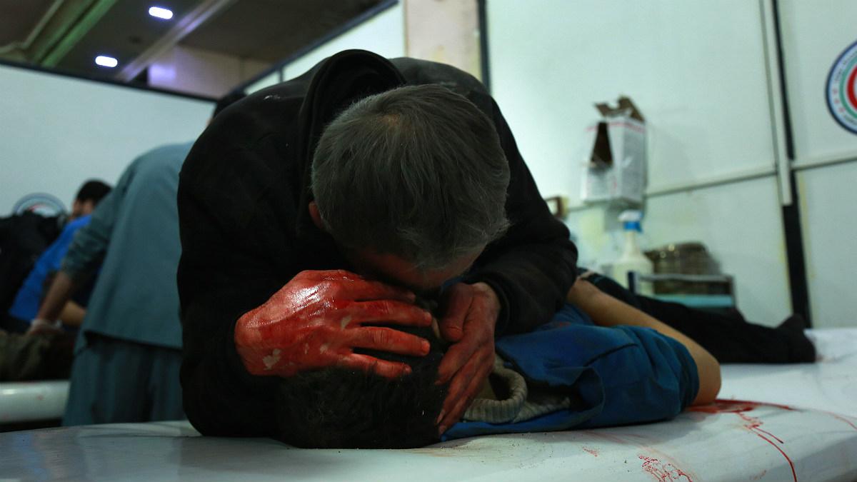 Un hombre llora sobre el cadáver d eun niño en Ghuta Oriental tras los bombardeos del régimen sirio. (AFP)