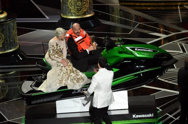 Mark Bridges, ganador del Oscar a mejor vestuario, con Helen Mirren sobre la moto acuática que ganó por realizar el discurso más corto. Foto: AFP