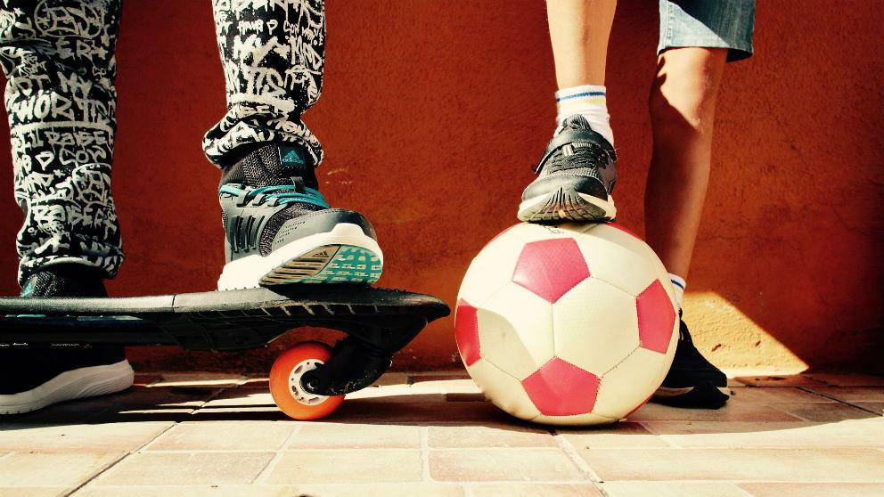 Niños en el patio de un colegio con una pelota de fútbol.
