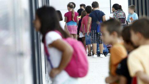 Menores entran en su centro escolar para dar comienzo a las clases.
