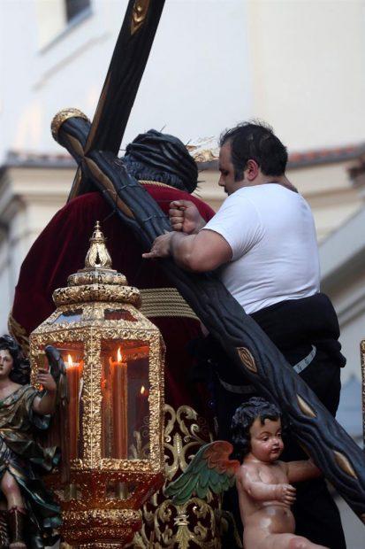 Un costalero encima del paso de la Hermandad de Jesús del Gran Poder en Madrid, arreglando temporalmente la cruz del paso que se rompió al chocar contra un semáforo. Foto: EFE