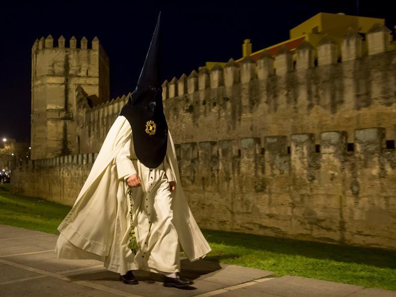 Un nazareno de la Hermandad de La Macarena se dirige al Templo para efectuar su estación de Penitencia en la Madrugá, la noche grande de la Semana Santa de Sevilla.