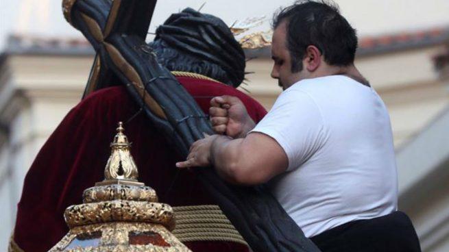 Un costalero arreglando la cruz del Jesus del Gran Poder de Madrid
