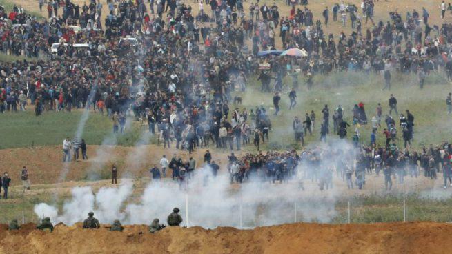 Una foto tomada el 30 de marzo de 2018 desde el kibutz israelí sur de Nahal Oz, al otro lado de la frontera de la franja de Gaza, muestra granadas de gas lacrimógeno que caen durante una protesta campal palestina conmemorando el Día de la Tierra, con soldados israelíes en primer plano. Foto: AFP