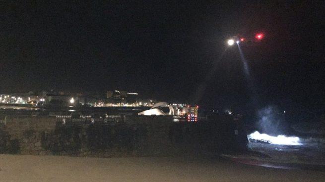 Un helicóptero de las fuerzas de seguridad iluminan la playa del Orzán, en A Coruña, donde esta noche una joven ha desaparecido. Foto: Twitter